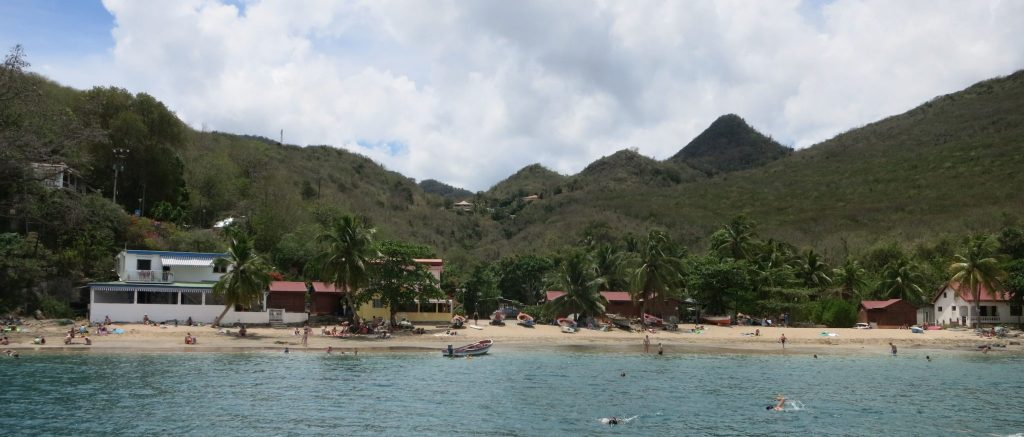 a view of the beach with a few small buildings and palm trees, with mountains behind them
