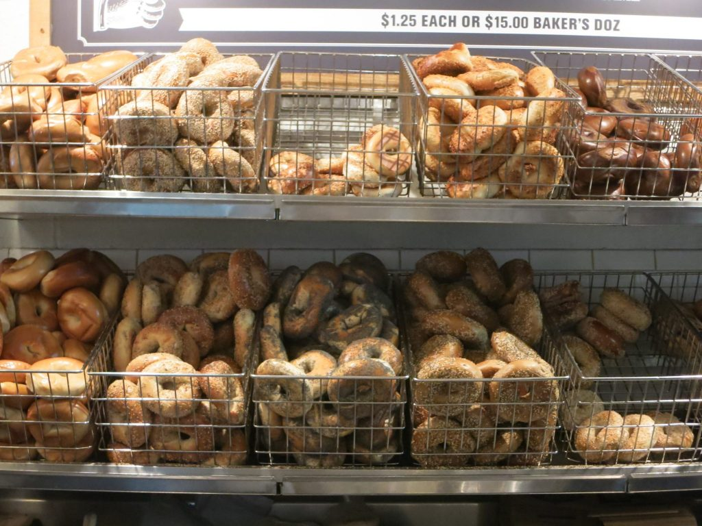 """Lots of different types of bagels, displayed in two rows of baskets in a bagel store. """"$1.25 each or $15.00 baker's doz"""""""
