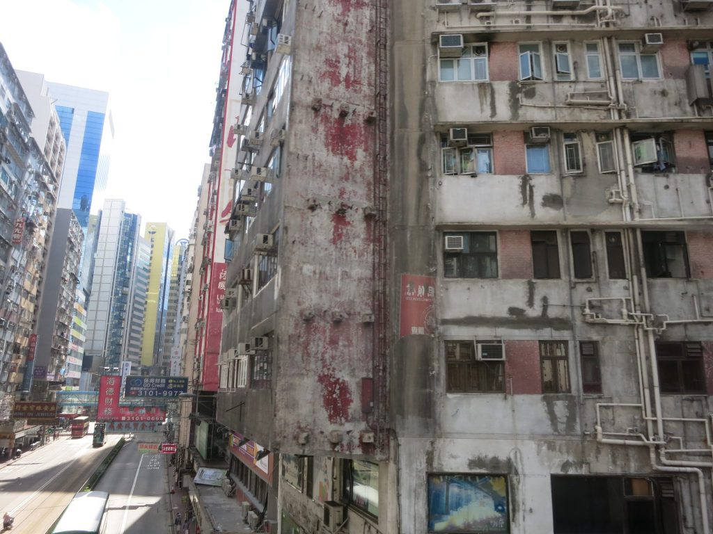 rundown exterior of a building in Hong Kong. The paint is long gone, and it looks like some of the concrete is coming off. In some spots it looks like the concrete has been patched. Many windows have small air conditioners protruding out. Pipes of various sizes run both vertically and horizontally between the floors.