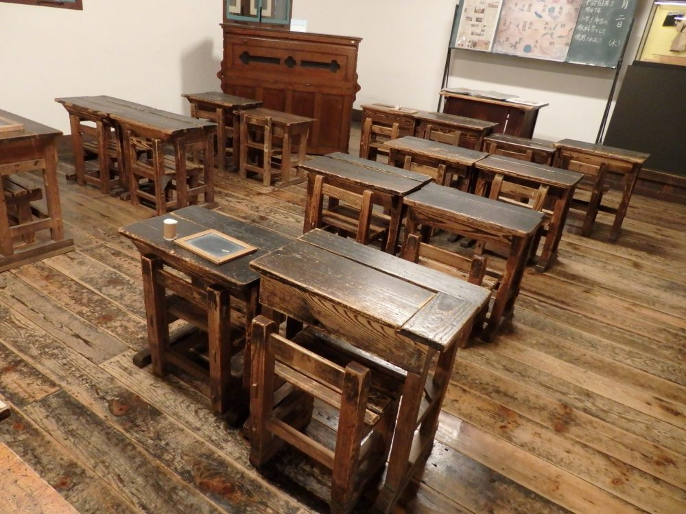 old-fashioned wooden desks are lined up two by two in a classroom in Kaichi School, Matsumoto