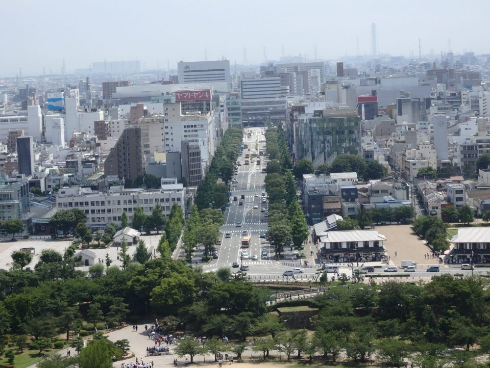 Things to do in Himeji: looking down the same boulevard from Himeji Castle toward the train station: the boulevard is wide and the buildings are typical uninteresting city buildings.