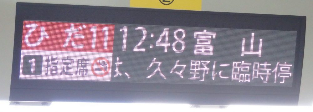 train station sign in Japanese. The only recognizable parts if you don't read Japanese are the numbers 1 and 11 and the time 12:48 and the symbol for no smoking.