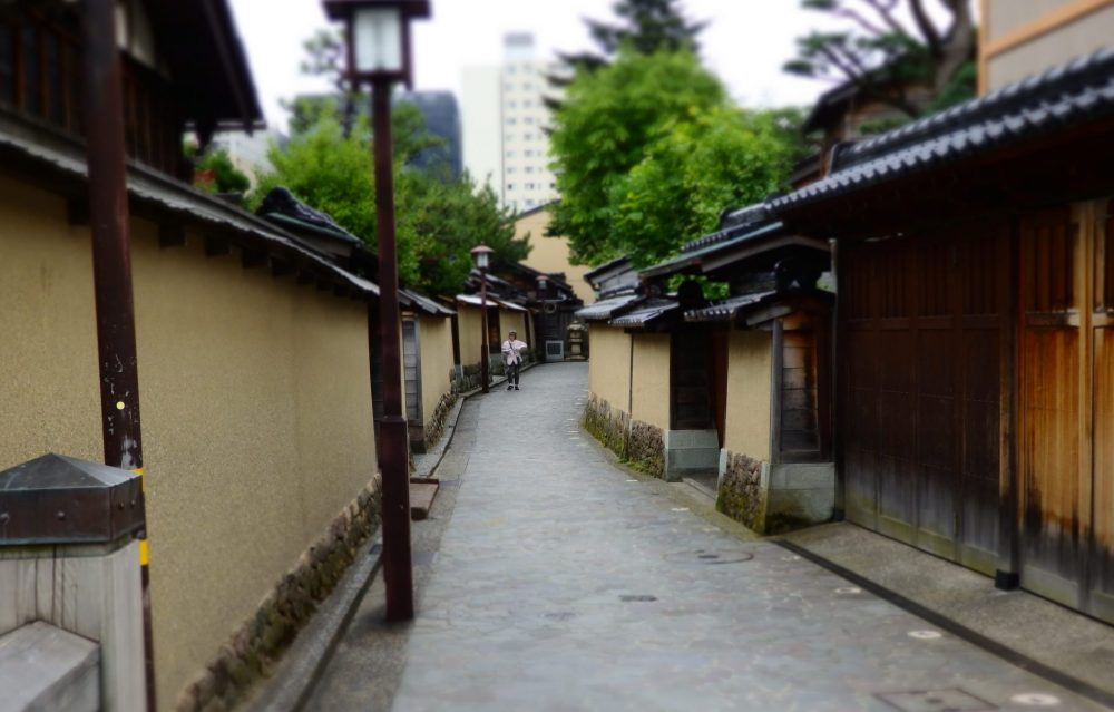 a street in the Nagamachi neighborhood of Kanazawa: low buildings on either side with light brown plastered walls and brown roofs. No windows are visible. The road curves out of sight and a tall modern building is visible in the distance. Is Kanazawa worth a visit?