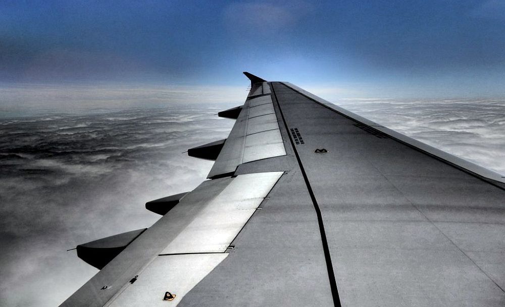 Looking out of a plane along the grey wing. Blue sky in the background, a cloudy sky below.