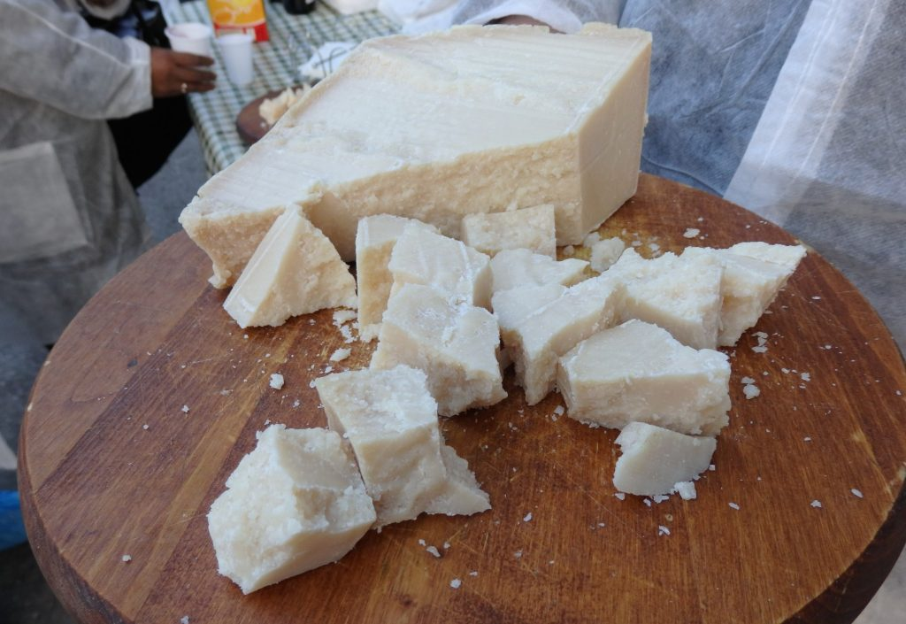 A large chunk of cheese on a wooden board, with smaller, crumbly looking chunks next to it.