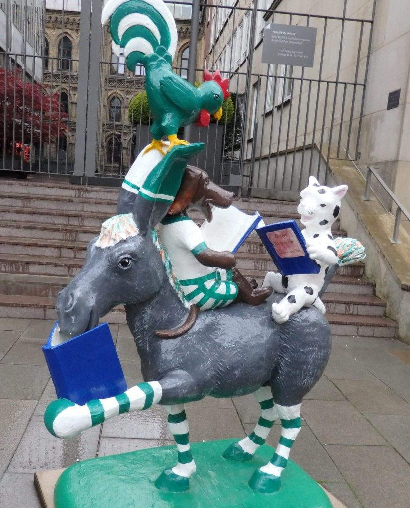 an image of the town musicians of Bremen, in this case, reading books