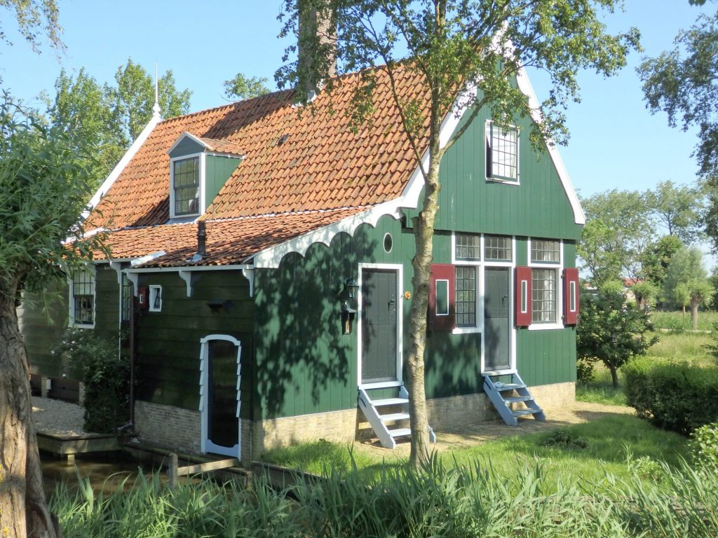 The small house is covered in wood, painted green, but with white decorative trim around windows, doors and roofline and with little dark red shutters. The roof is terra cotta yellow tile. EAch of the two front doors has three ladder-like steps leading up to it.