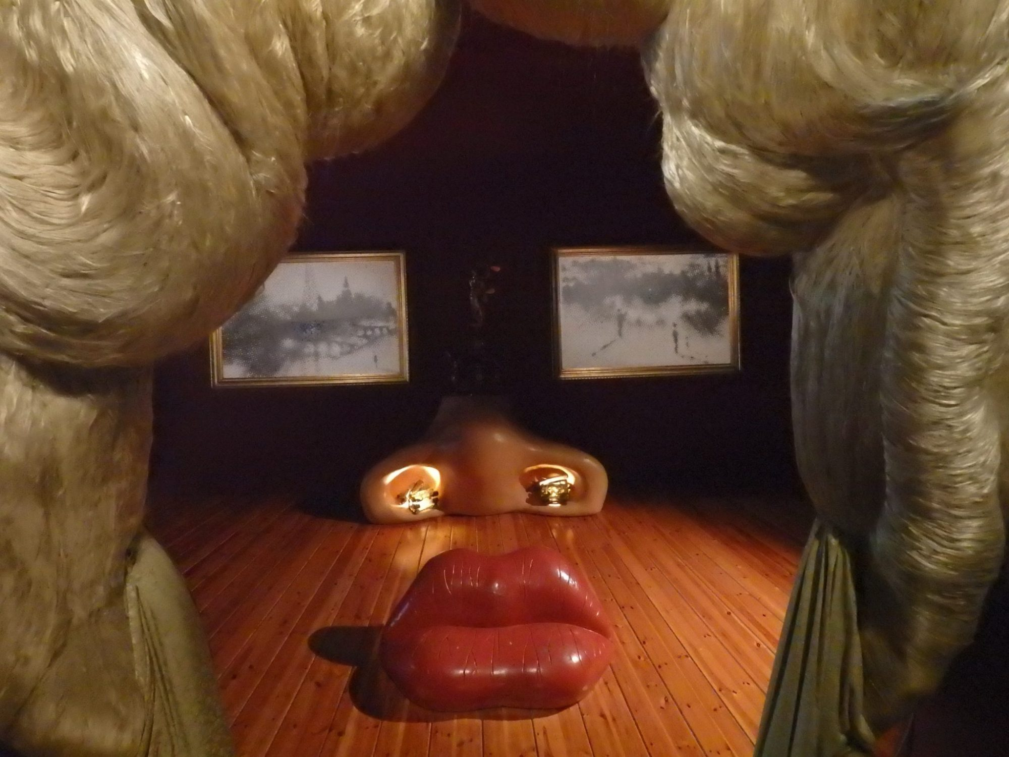 """The """"hair"""" fills the left and right sides of the photo. Ahead, on the floor is the lip-shaped sofa. Behind that, the shape of a nose, lit up from inside the nostrils. On the wall behind that: two horizontal paintings that are indistinct, but from this vantage point look like eyes."""