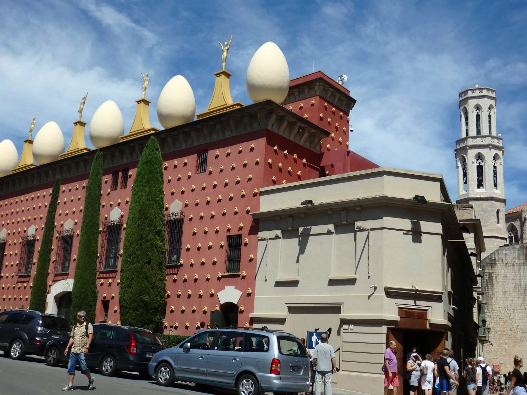 The outside of the building is dark red, with gold-colored bumps (actually a fat human figure from close up). Along the top is a row of large white eggs taller than a person. Between the eggs are a series of statues on pedestals painted gold.
