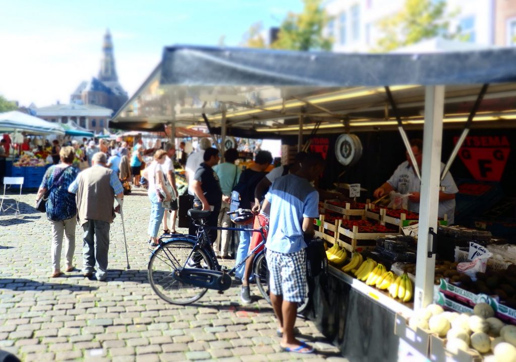 A market stall with fruit on display. Several people face the fruit seller inside the stall. One of them holds a bicycle. An elderly couple walks down the row away from the camera. In the blurry distance, more of the market is visible, with a blurry view of a church tower beyond that.