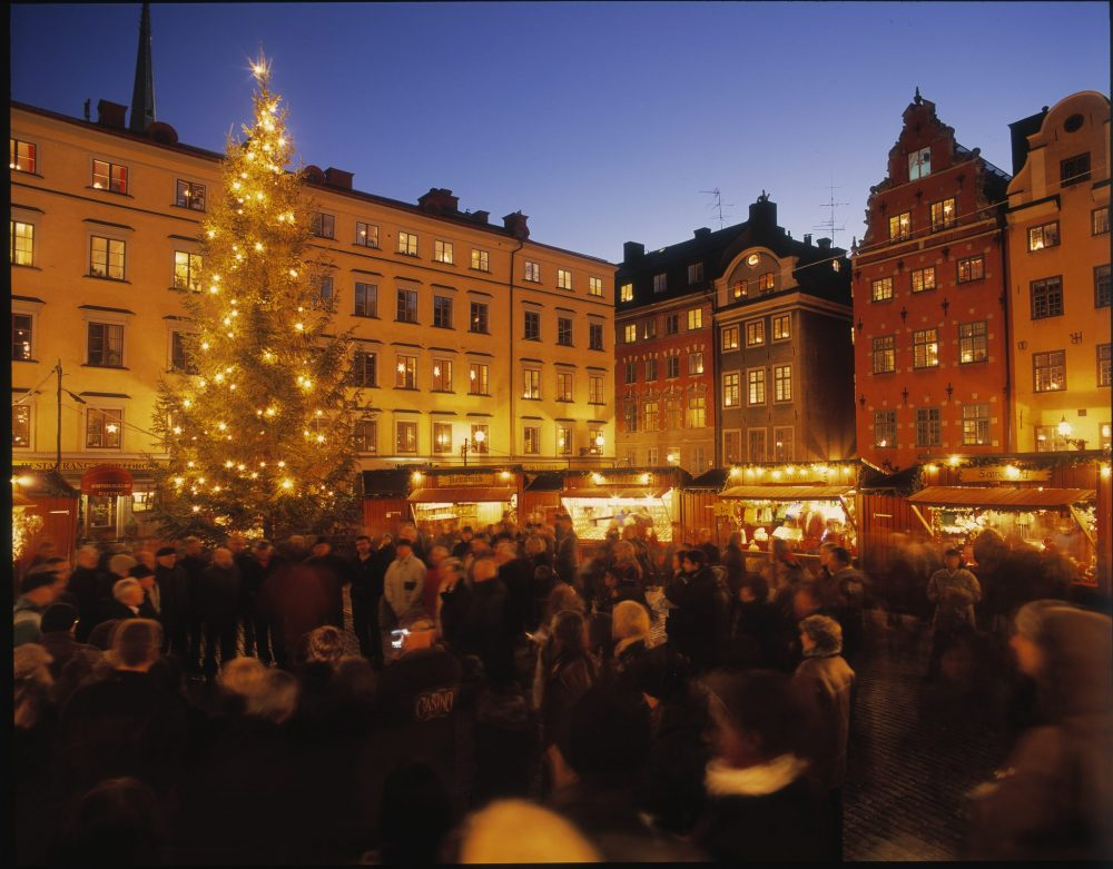Two sides of the square are visible: old buildings, their windows lit up and the night sky behind. Below is a row of brightly-lit stalls and a crowd of people as wel as a tall Xmas tree lit with white lights. photo by Jeppe Wikström/ mediabank.visitstockholm.com