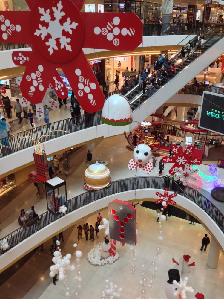 a shopping center in Chiang Mai, Thailand, looking from one of the floors into the open atrium in the middle of the mall. Oversized Xmas decorations hang in the atrium. Below, on the bottlm level, round white balls surround a snowman. Photo courtesy of Jane Dempster-Smith