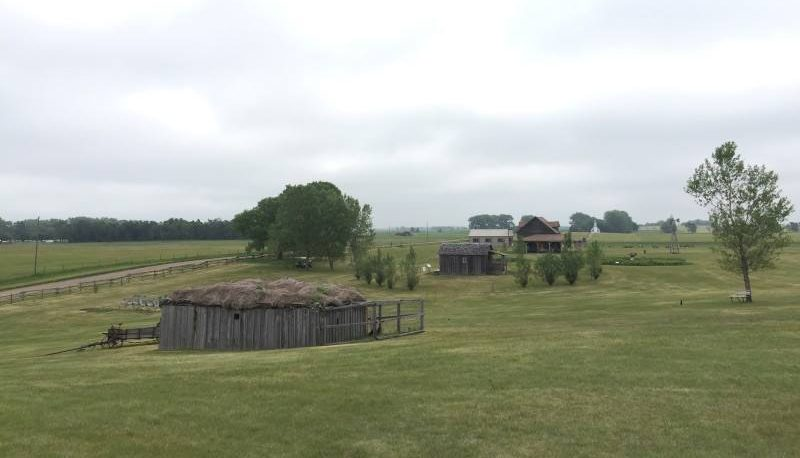 In the foreground, what looks like it might be a barn of some sort: grey wooden sides and a sod roof. Beyond it, across a flat grassy field: 3 more houses. One looks like a one-room wooden house. The other two look more substantial: one painted white, single story; one brown one with two stories and a veranda.