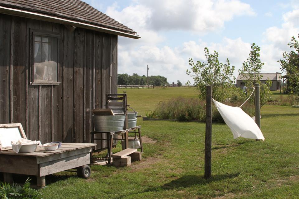 On the left part of a building is visible: brown, unpainted wood siding and a brown shingle roof. Next to it are various objects related to doing laundry: metal pails, a washboard in one of them. A crank-handled wringer, and a short clothesline with a white sheet hanging on it. Behind is a flat green field.