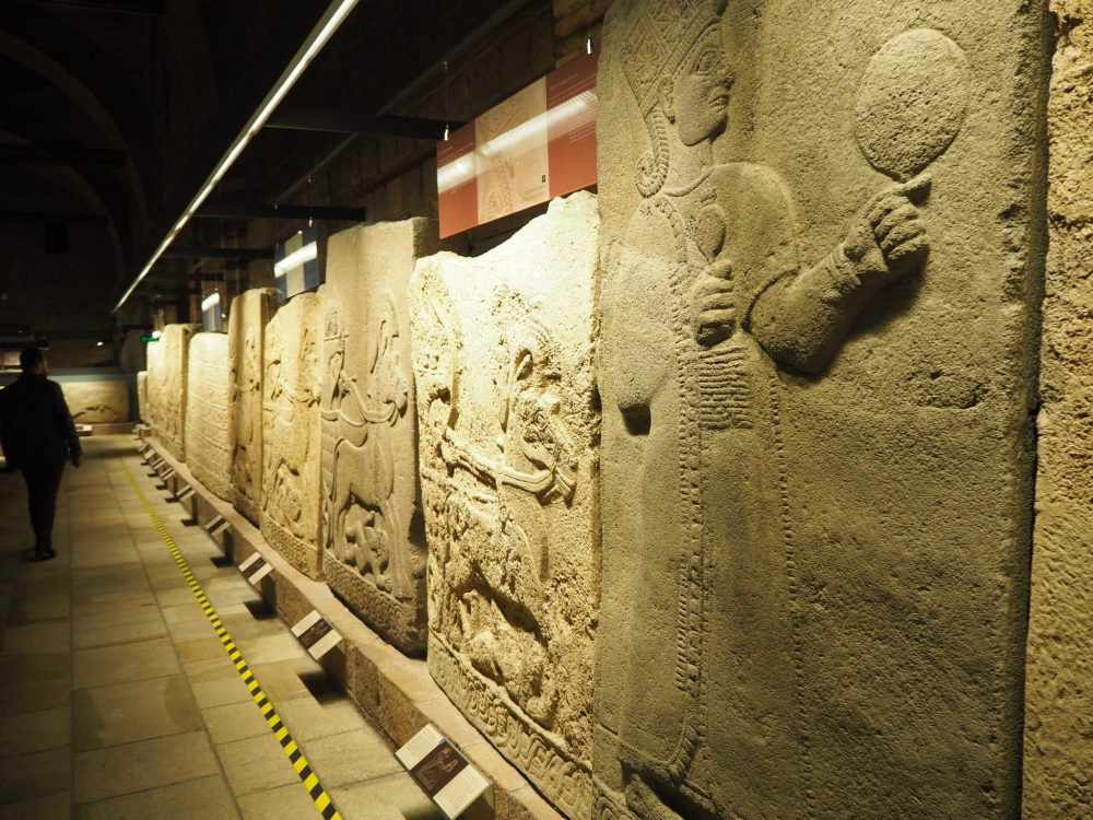 The orthostats stand against a wall in a long line, and are well lit from the left. The nearest shows a person in a long robe holding what looks to be a ball, but may be a hand mirror. On the two orthostats next to that one are horses galloping, presumably portraying a battle. The rest of the rown are not clearly visible in this picture.