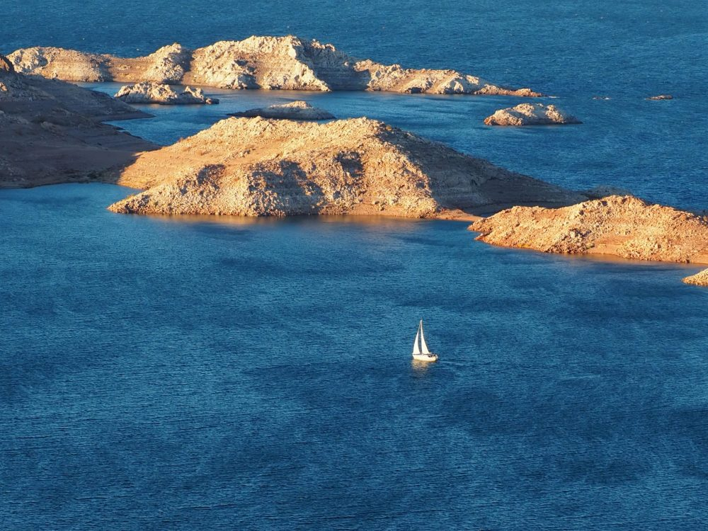 A lone sailboat on Lake Mead in December: bright blue water: rocky islands with no green, a sailboat with two sails.