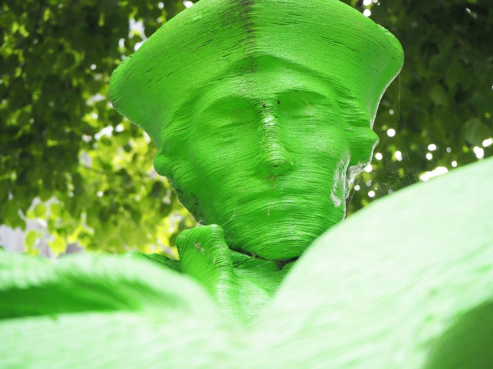 In this bright green close-up of Erasmus's face, the layers of the plastic 3D print are clearly visible.