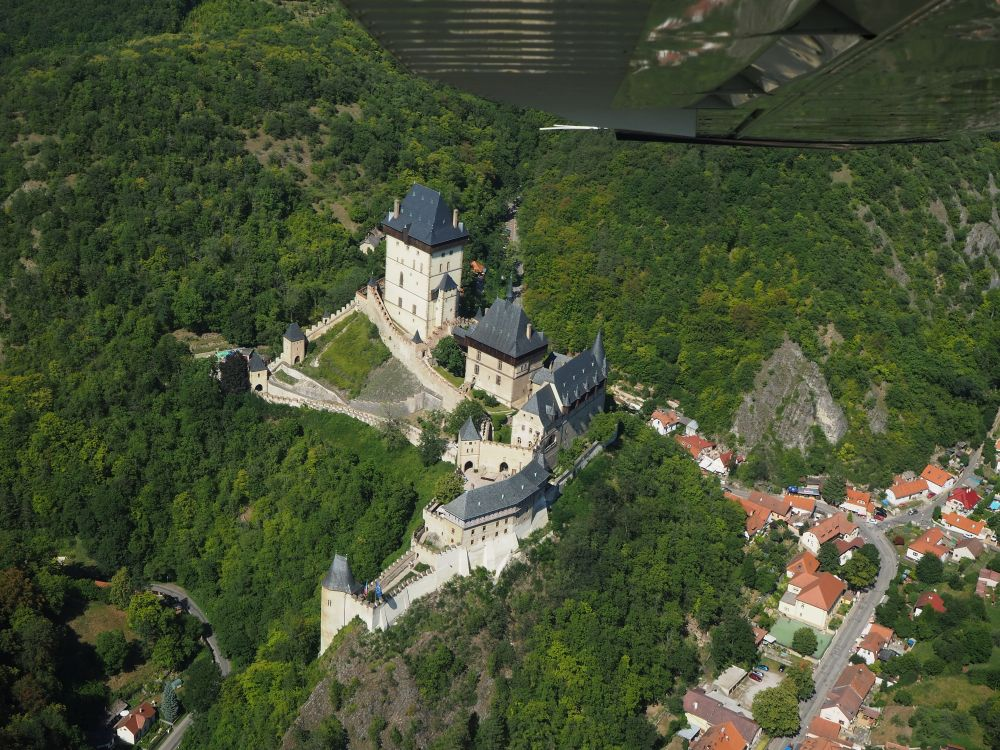 Karlstejn Castle sits on a hill currounded by green forest. It's basically 4 buildings, all with white walls and gray roofs. Two are tower-like, one taller than the other. Walls are visible abour the top of the hill. In the left bottom corner the village is visible, along a road.