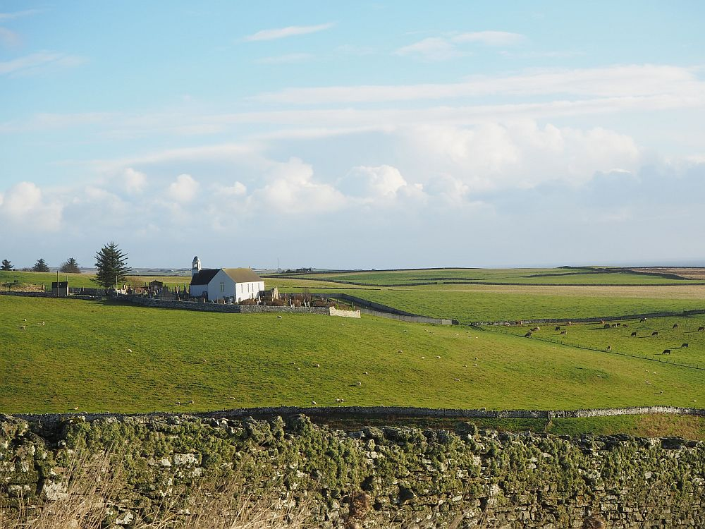 a view of a church and farm fields somewhere in the eastern Scottish Highlands
