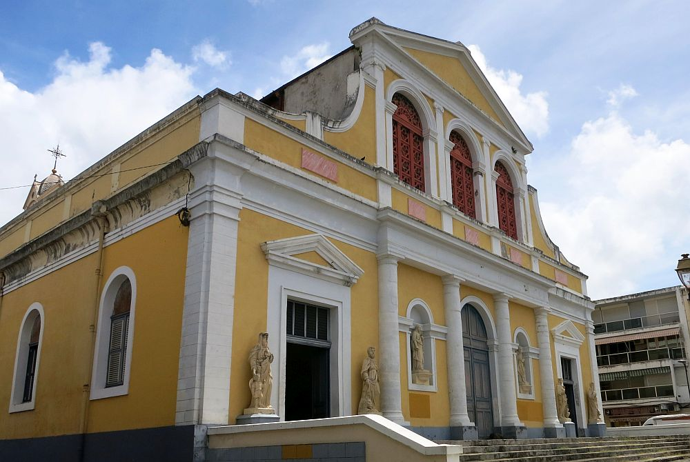 The cathedral of St. Pierre and St. Paul in Pointe-à-Pitre: The building is yellow with white edging. The ground floor has three doors, symmetrically placed; the center one has an arched top. White pillars separate them and the two statue niches between doors. The upper floor is narrower, with three arched windows and a pointed pediment.