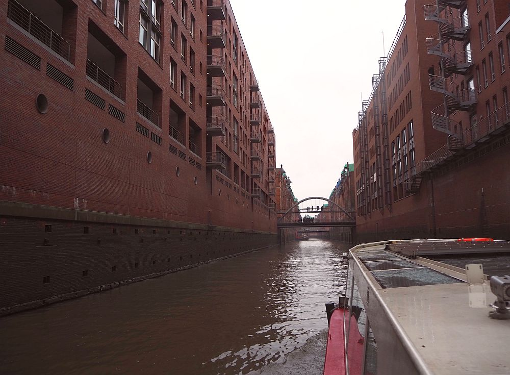 red-brick warehouse buildings line the canal, and a small arched pedestrian bridge is visible ahead. Hamburg for a weekend.