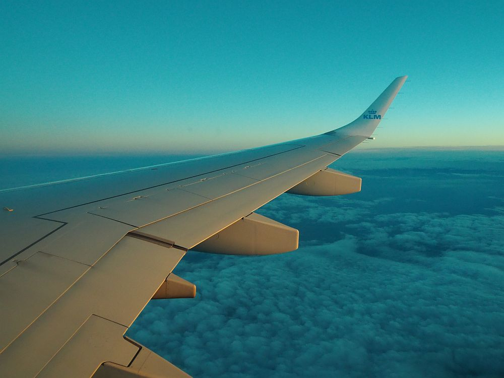 a view of an airplane wing over fluffy clouds, with a sunset sky in the background