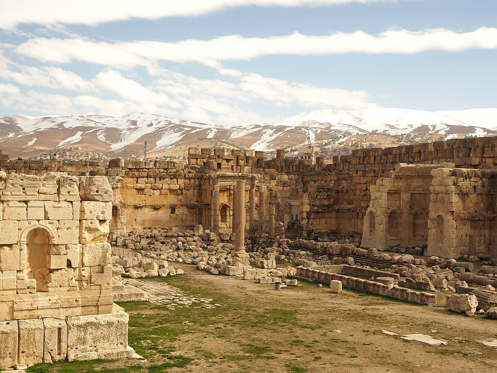 The outer walls of the complex look intact in this shot, with the neat Roman-era stone for most of the wall, but with just a few rows of rougher, darker stone on top of that. The rubble seems to be in neat lines in this part of the complex. Baalbek ruins, Lebanon.
