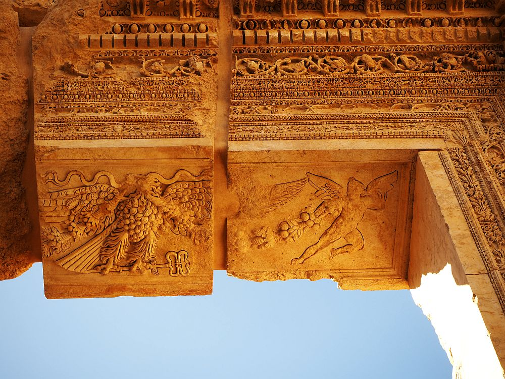 The carvings show a winged person (Bacchus?) pulling along what might be grape vines. Next to that is a figure that seems like a cross between a bunch of grapes and an eagle. Temple of Bacchus at Baalbek UNESCO site.