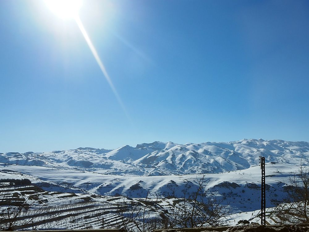 High mountains in the distance, covered in snow against a blue sky. Highlights of Lebanon.