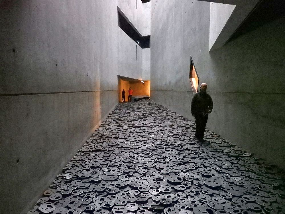 An unevenly-shaped space with concrete walls and a high ceiling, where the floor is piled with round, metal faces with screaming mouths.