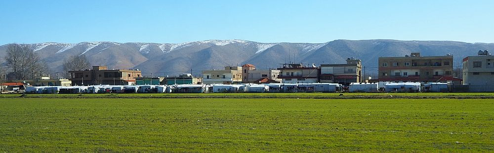 At the far side of a green field is a low line of white tents, with buildings behind them and mountains in the background.