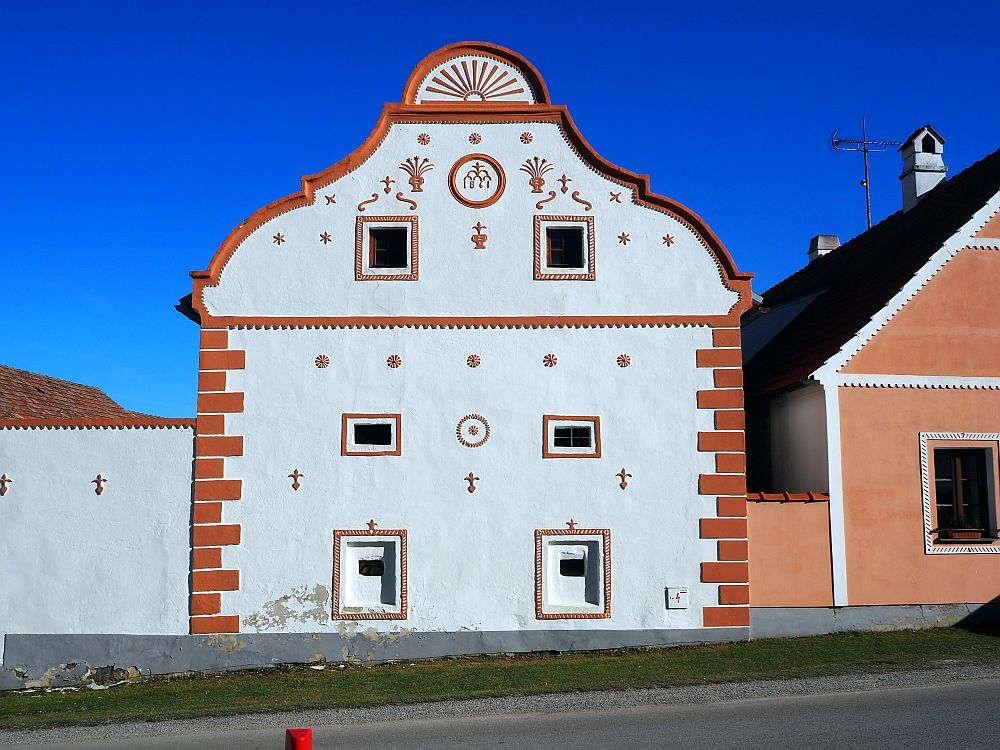 A simple square house with a peaked roof: white paint with pinkish accents.