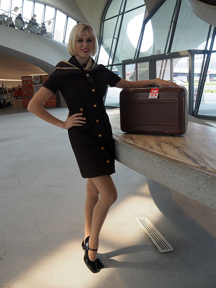 The attendant's outfit is brown and close-fitting, with a mid-thigh-length skirt and short sleeves. She wears black pumps and leans on a small suitcase.