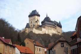 a typical fairytale castle: with a tower and defensive crenellations on its walls, perched high on a hill above the village visible in the foreground: Visiting Karlstejn Castle from Prague