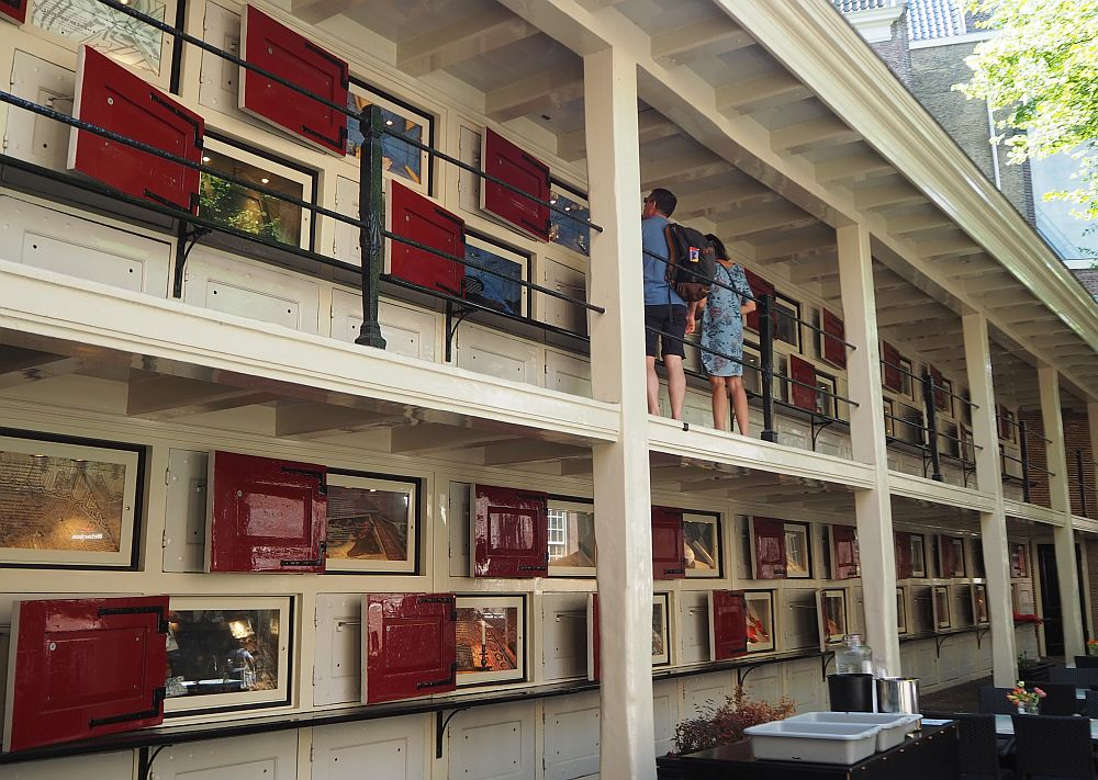 The lockers are arranged along a wall, in two rows on the ground floor and then two more rows along a gallery upstairs. Each has a red door, now open to show the exhibits in each one.