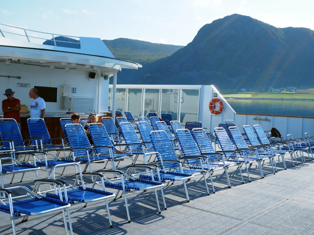 A flat open floor on level 7 of Hurtigruten's MS Nordnorge, with several rows of lawn chairs, mostly empty. Mountains visible in the background.