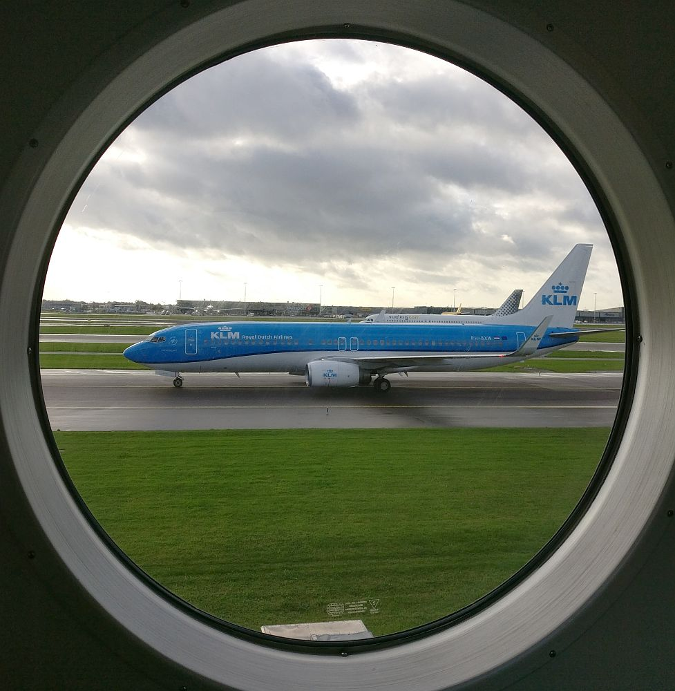 Looking through a round airplane window, a blue and white KLM jet taxis by on a neighboring runway. Partly cloudy sky overhead.