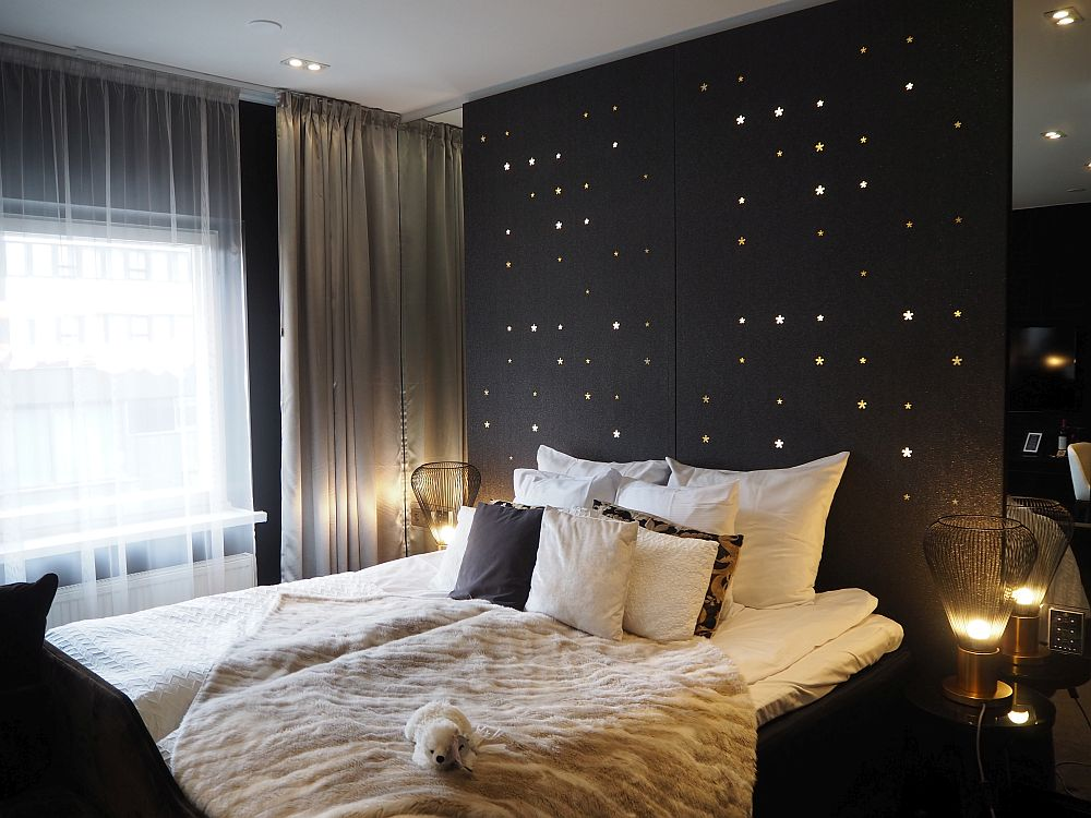 The bed is made with white sheets and a white fuzzy blanket lies diagonally across it, with a small stuffed animal (a polar bear) sitting on it. A lot of pillows are piled at the head end of the bed, and the whole wall behind it is dark brown, but with small, star-shaped lights here and there.