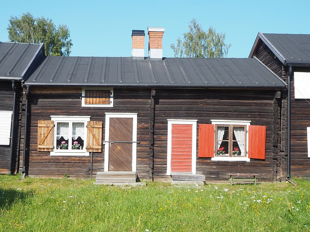 Two small houses fill the photo, with a bit of green grass in front. Each has one door with one window next to it. The left-hand one is brown with white-trimmed windows and brown shutters and door. The right-hand one is the same but the shutters and door are painted an orangy-pink color.