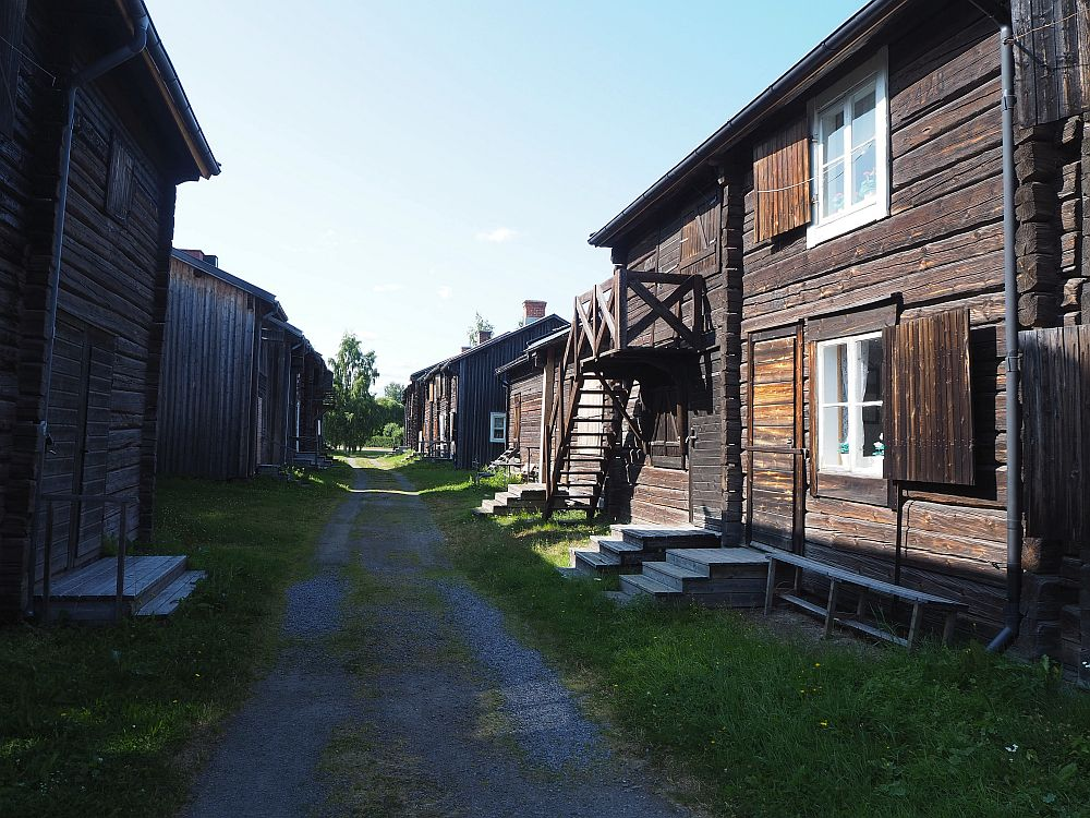 A view down a Bonnstan road. On either side: dark brown houses of flat-cut logs. Windows are trimmed in white, with brown shutters. Some houses are single-story, some are two-story. One house, on the right, has a staircase crossing the front to the upper floor.