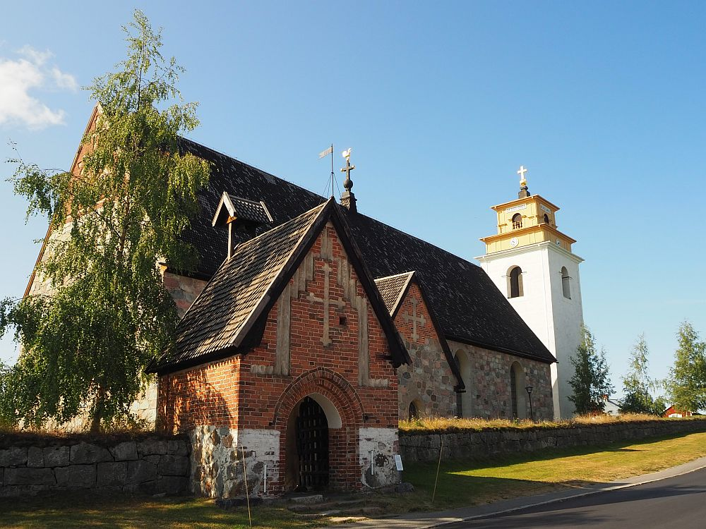 The stone church in Gammelstad church town. An archway leads to it in the foreground and a white bell tower is visible behind it.