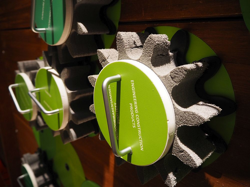 """Close-up of a single gear with a handle in the middle, labelled """"Engineering construction products."""""""