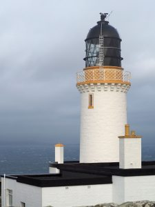 A tall white lighthouse against a grey sky. The tower is white and cylindrical. On top is a brown-painted balcony, and above that is a black dome which, presumably, holds the light.
