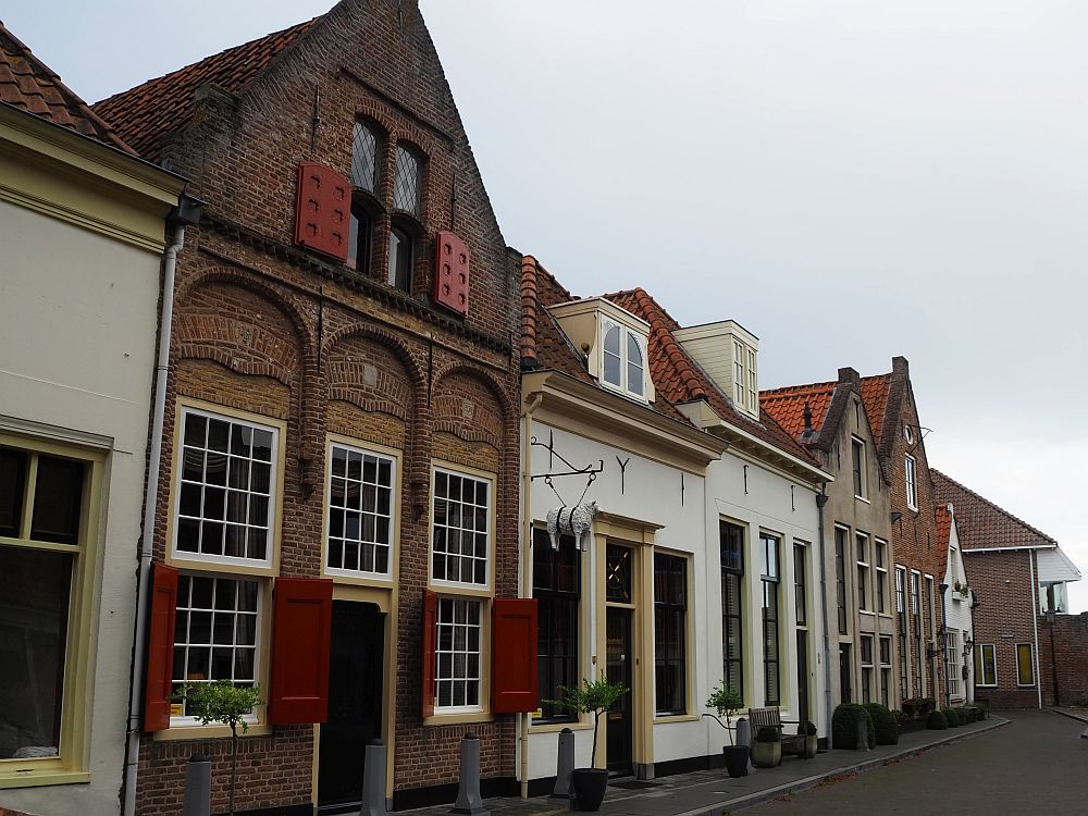 A row of little houses: some red brick and some painted white. One has a shop sign sticking out from it that is a carving of a sheep.