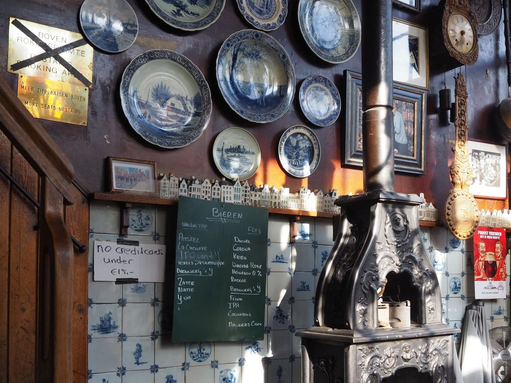 The upper half of the wall is brown wood panelling hung iwth china plates. The bottom half is tiled with delft tiles, blue figures on white. A narrow shelf divides the two halves and holds a row of delft ceramic houses. In front of the wall is a cast-iron stove with a stovepipe extending straight upward. This cafe was the first stop on the Jordaan food tour.