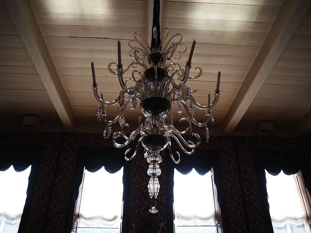 This chandelier is particularly elegant: just arms of crystal in several tiers that curl down and then up. Some of them hold candles. Some of them have a single hanging ornament of crystal.