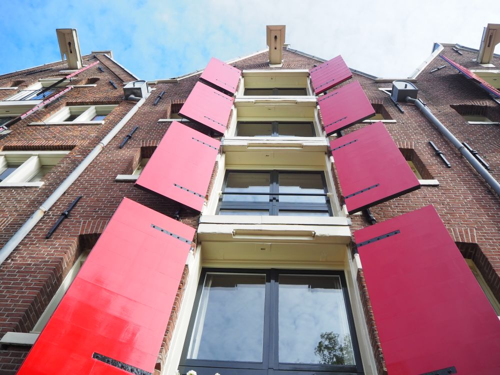 Looking up at the building, the center of the picture is a vertical column of windows, each with open red shutters on each side.