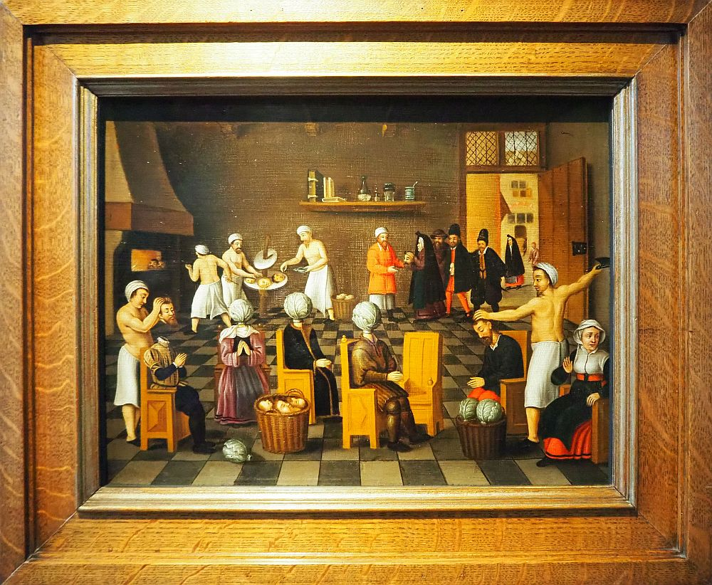 The Legend of the Baker of Eeklo painting. In front are the people with cabbages rather than heads. They sit in a row of chairs. A man on the right is holding a knife high, about to slice off a man's head. A man on the left is holding a head over a sitting torso, about to place the head back on. Behind on the left is a fireplace and a shirtless man is placing heads inside it with a long paddle. Two other men are preparing heads on a table. On the right rear people in black coats are lined up and a man in a red coat receives them.