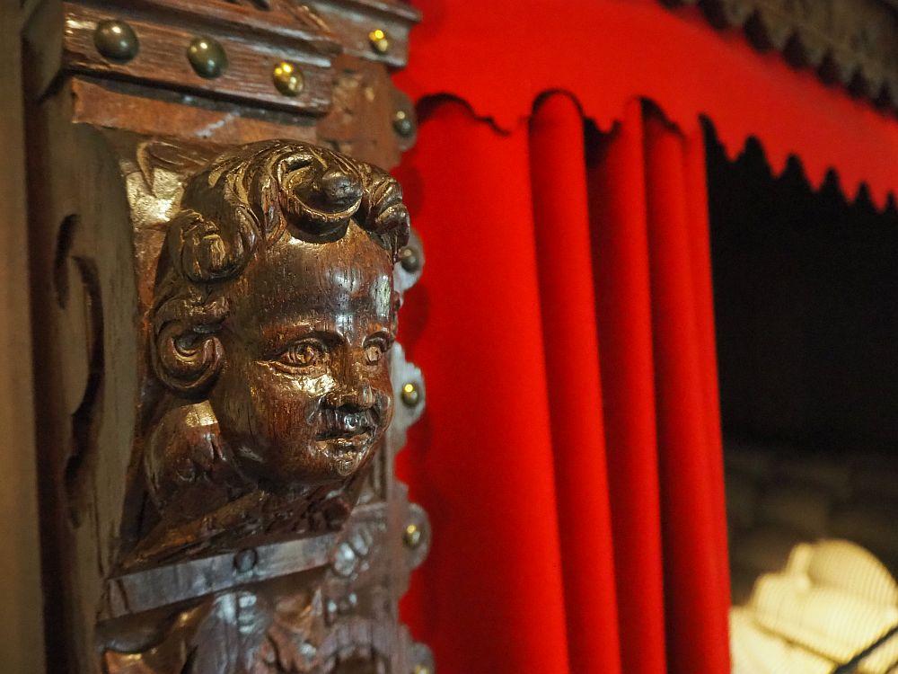A dark wood carved cherub's face. Behind that, a red curtain.