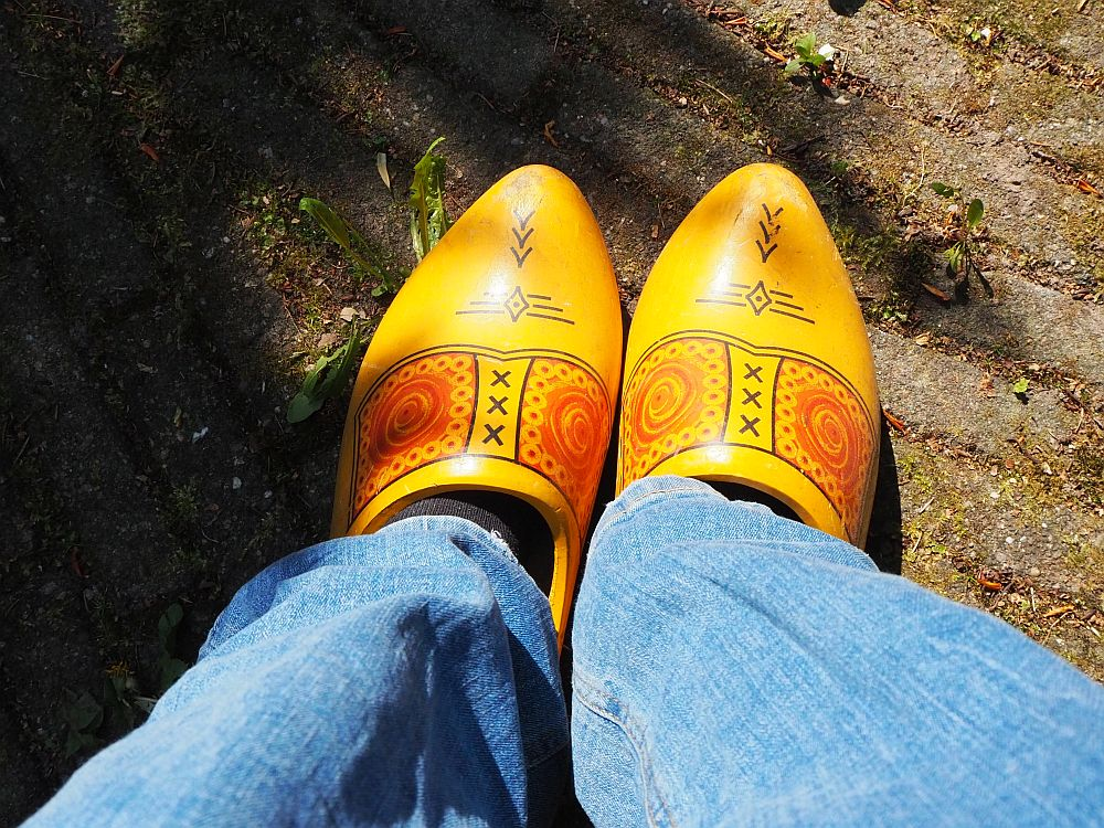 Americans see the Dutch as clog-wearers. The photo looks down at my feet: the bottoms of my jeans are visible, and the clogs are yellow with some red and black decorations. The ground is brick-paved.